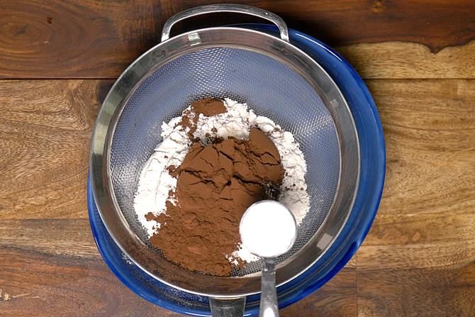adding dry ingredients to bowl to make eggless chocolate cake