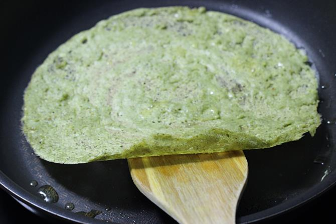roasting on both sides for crispy pesarattu