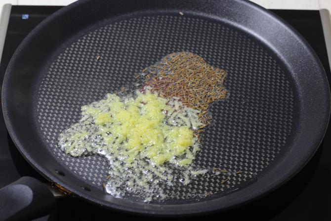 tempering cumin on a tawa for tawa paneer