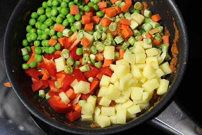 sauteing mixed vegetable curry in pan