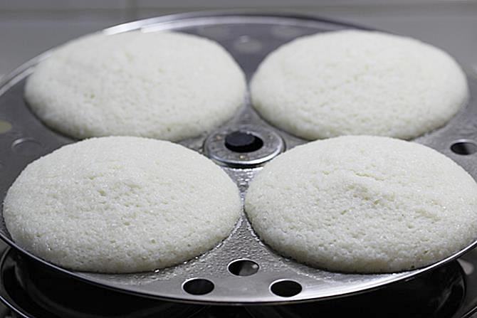 placing the plates inside a steamer to make soft idli recipe