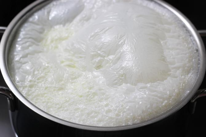 boiling milk in a pot for sandesh recipe