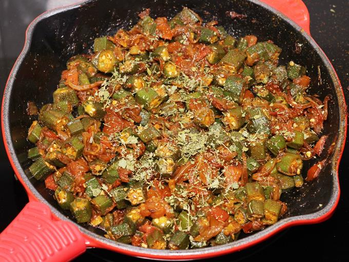 sprinkling kasuri methi to make bhindi ki sabji