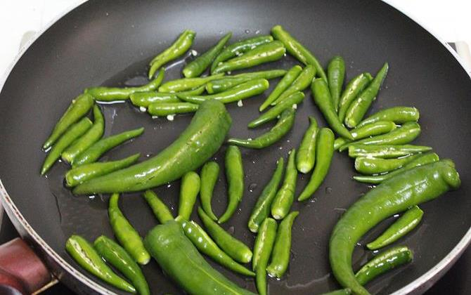 frying chilly in oil to make green chili chutney
