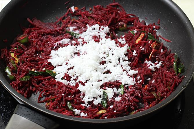 addition of grated coconut to pan for beetroot stir fry