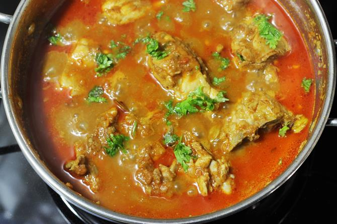 Garnishing chicken curry with coriander leaves