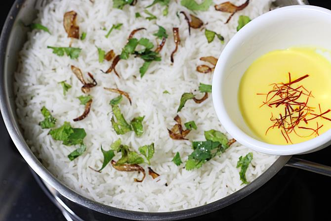 addition of rice, herbs for making hyderabadi dum biryani