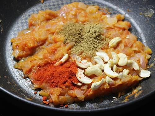 adding spice powders to make paneer butter masala
