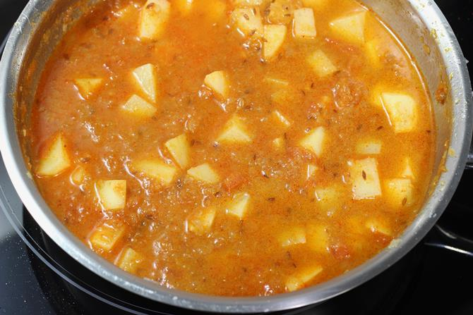 pouring water for potato curry recipe