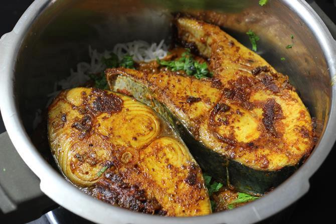 layering fried fish over the gravy for fish dum biryani recipe