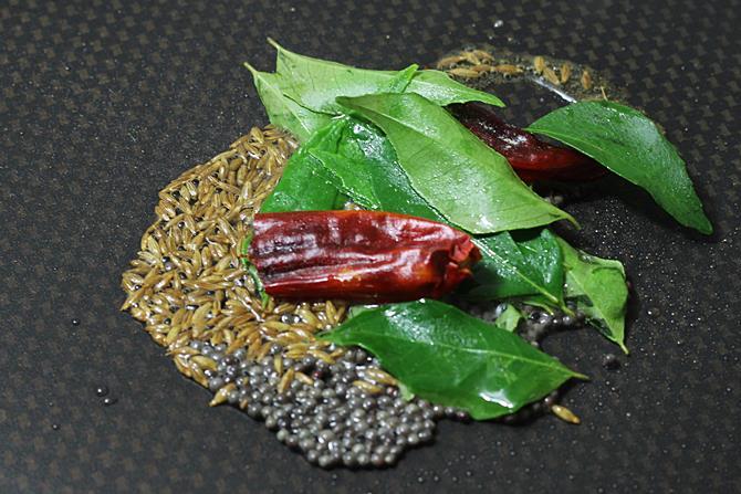 seasoning with tadka spices to make lemon rasam recipe