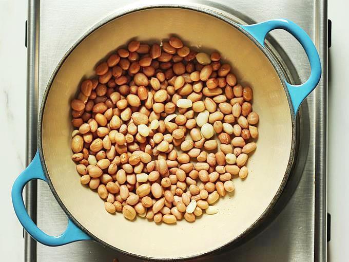 adding peanuts to pan to make groundnut chutney