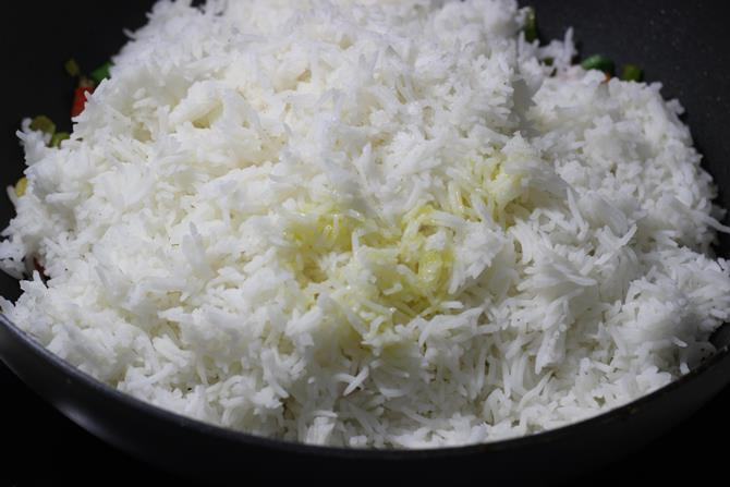 cooked and cooled rice added to the pan to make schezwan fried rice recipe