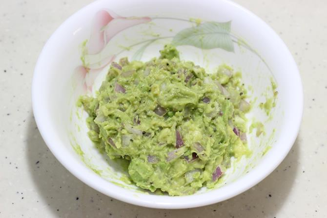 mashing fruit to make chunky guacamole for sandwich