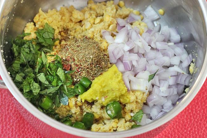 adding onions chilies herbs to make masala vada