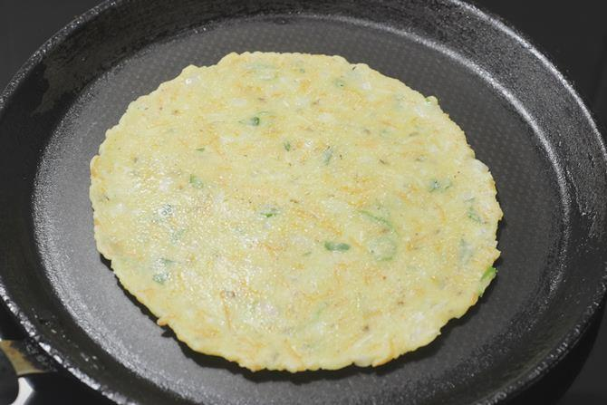 flipping and toasting akki roti on a tawa