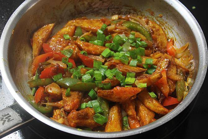 sauteing chilli potato with spring onions