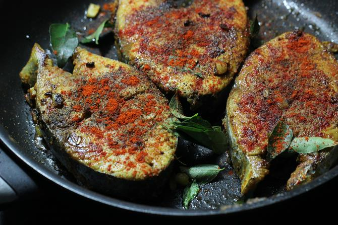 Add ghee to a hot pan, Add fish, curry leaves and begin to fry on a medium flame