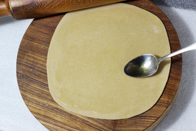 smearing ghee on paratha layer