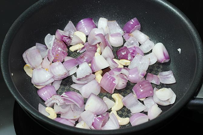 frying onions cashews to make kadai paneer gravy recipe