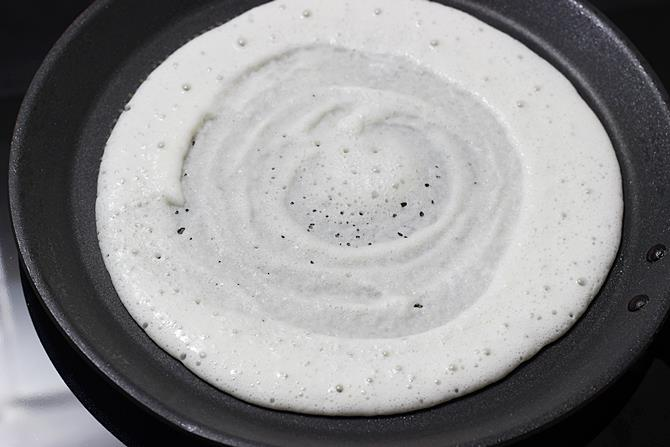 spreading batter to make egg dosa recipe