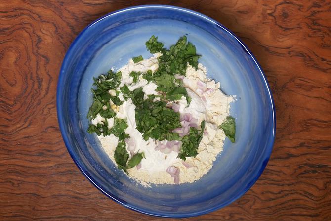 adding onions coconut coriander to make mysore bonda batter