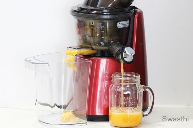 making orange juice in a slow juicer