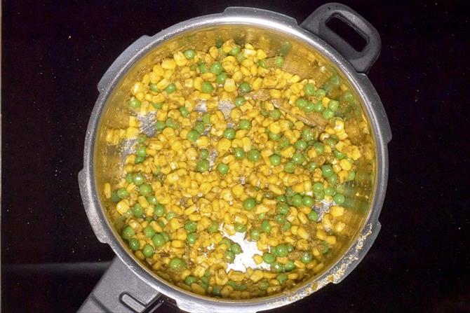 frying corn peas to make corn pulao