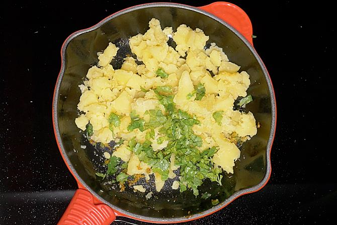 adding coriander leaves to make batata vada stuffing