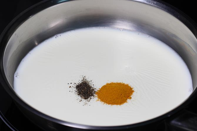 adding turmeric and pepper to make haldi ka doodh