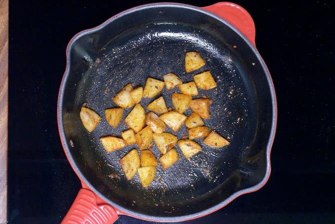tossing spiced potatoes until crisp to make aloo chaat