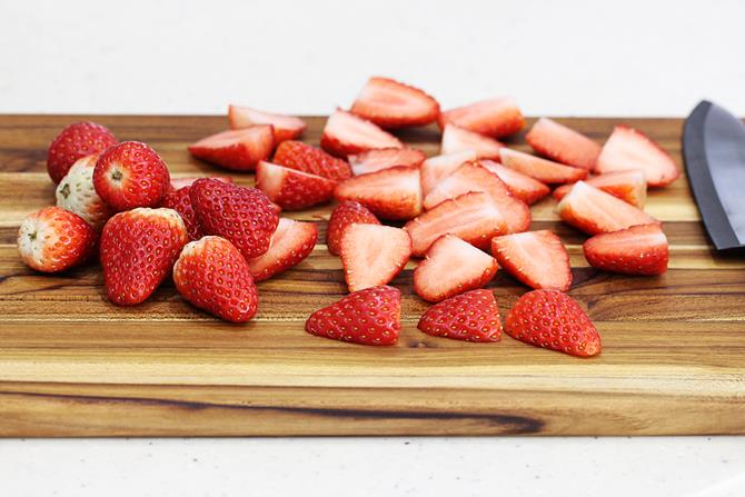 sliced strawberries on a chopping board