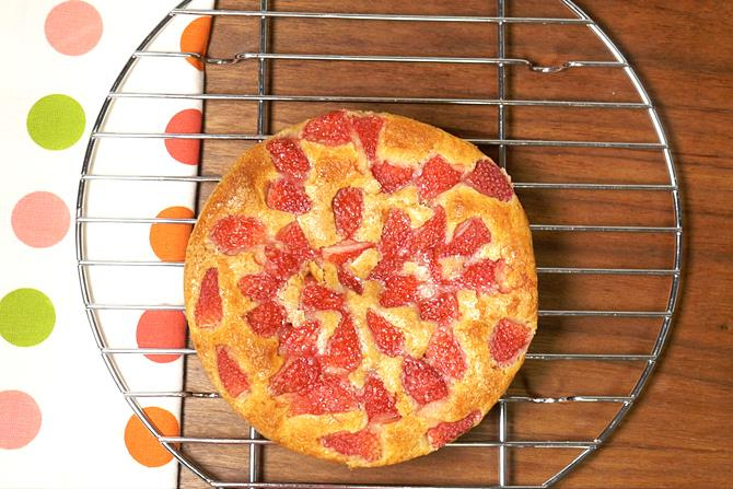 cooling eggless strawberry cake on a wired rack