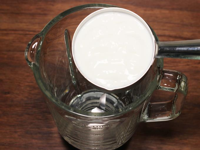 adding curd to a blender to make lassi