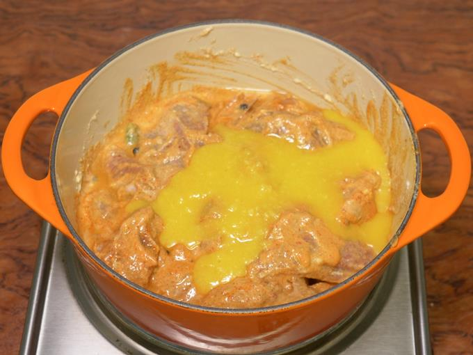 adding ghee to cook mutton korma
