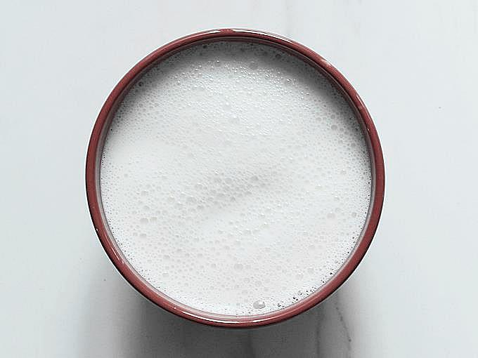 frothy milk in a bowl to make curd