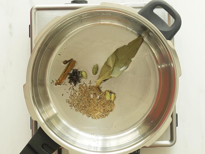 tempering spices in oil to make mushroom biryani