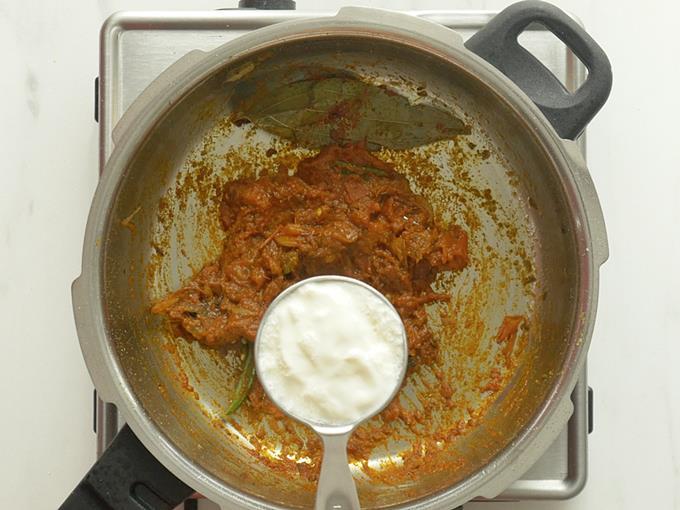 adding yogurt to make masala