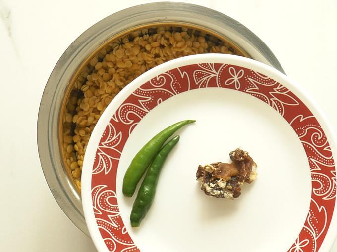 adding chilies tamarind to dal to make tomato pappu