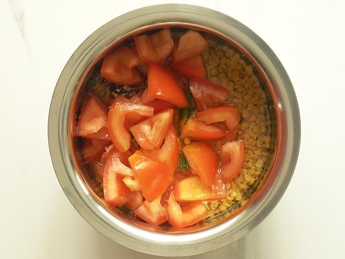 adding tomatoes to make tomato dal