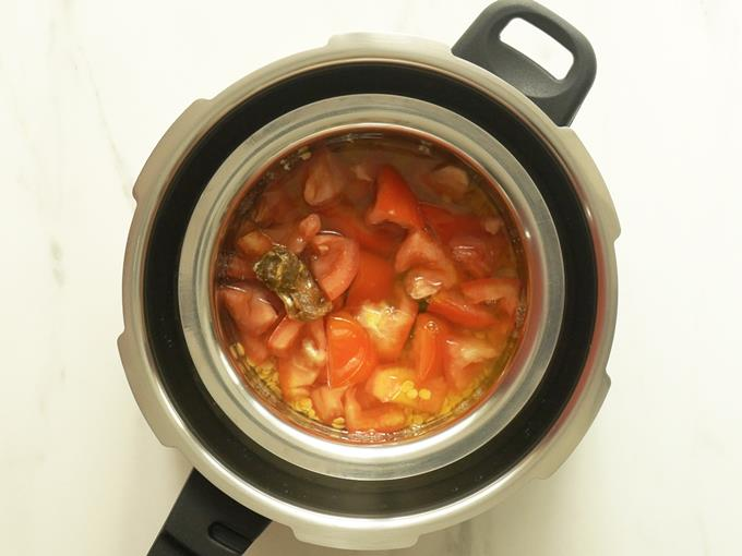placing the bowl in pressure cooker to make tomato pappu