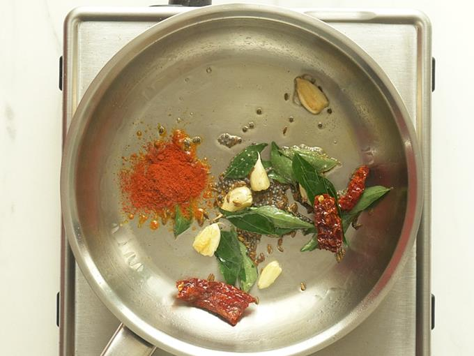adding garlic red chilies to make tomato dal