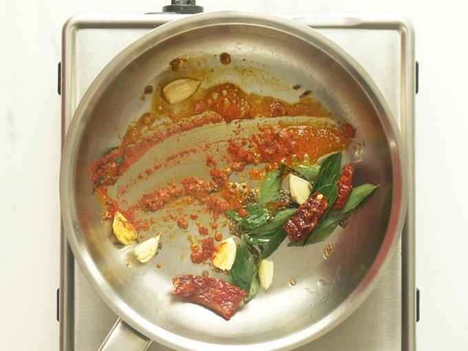 mixing the spices to add to tomato dal