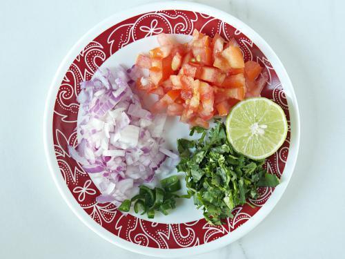 chopping onions tomatoes to make churumuri