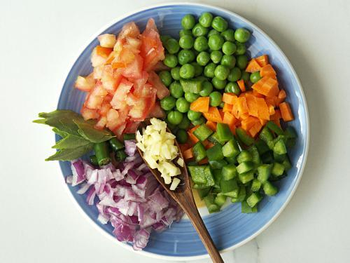 chopping veggies & ginger to make khara bath