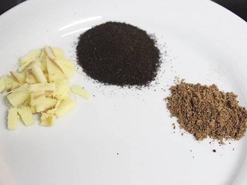 chopped ginger with tea powder & masala to make chai