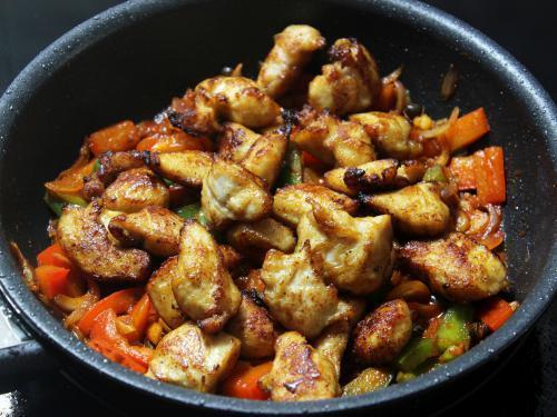adding fried chicken to sauce for szechuan chicken recipe