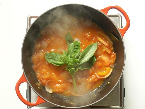 adding basil to pan to make tomato soup