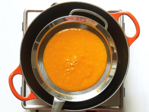 passing tomato soup through a strainer