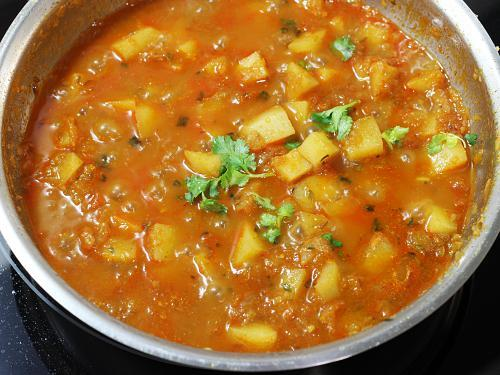 adding coriander leaves to potato curry